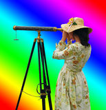 Girl with Telescope and Rainbow Colors. Girl in fancy dress and hat looking through telescope with background of rainbow colors Stock Photography
