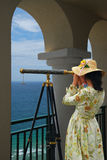 Girl with Telescope under Arches. Girl in fancy dress and hat looking through telescope at the ocean from a balcony under arches Royalty Free Stock Images