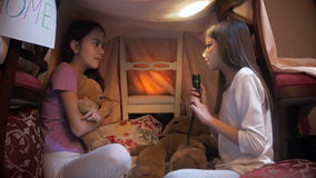 Girl telling scary story to her sister in selfmade tepee tent at night stock video
