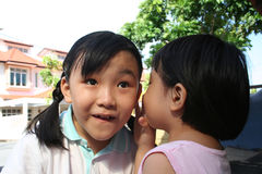 Girl telling secret. Little girl in pink telling another girl a secret stock image