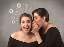 Girl telling secret things to her girlfriend Stock Photos
