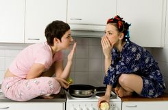 Girl Telling A Secret To Another - Gossip. Young women sitting in the kitchen and speaking royalty free stock photo