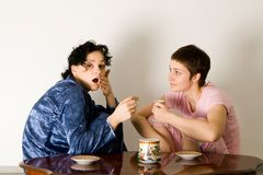 Girl Telling A Secret To Another - Gossip. Young women sitting in the kitchen and speaking stock photos