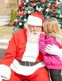 Girl Telling Wish In Santa Claus's Ear Royalty Free Stock Photos