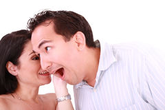 Girl tells something into surprised guy's ear Stock Photography