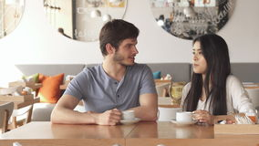 Girl tells something to her friend at the cafe. Pretty asian girl telling something to her male friend at the cafe. Long shot of couple of friends talking over stock footage
