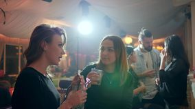 Girl tells something to her friend at the club with glasses behind bar counter on background of lights stock footage