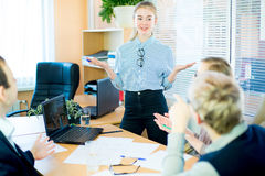 Girl tells something to his companions. Business team discussing at a table in an office, new business ideas. Two young men and two girls with glasses. Girl Royalty Free Stock Photos