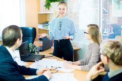 Girl tells something to his companions. Business team discussing at a table in an office, new business ideas. Two young men and two girls with glasses. Girl Royalty Free Stock Images