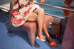 A girl with temporary henna tattoos on her legs. Sits in colorful dress on a chair on a cruise ship.  stock photos