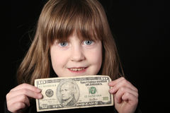 Girl with ten dollars. A brown haired girl holds a ten dollar bill up to her face Royalty Free Stock Images