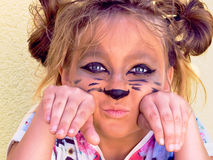 The girl of ten years, embellished cat face. School-age child cat face hands under his head. Wearing animal kitty girl baby game cute feline muzzle.Painted black Stock Photography
