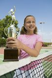 Girl at Tennis Net Holding Trophy Stock Photo