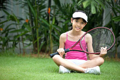 Girl with a tennis racket. Young girl with a tennis racket in the garden Royalty Free Stock Photo