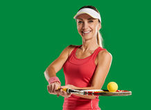 Girl with a tennis racket and ball. Successful sportswoman with racket. in a green screen studio.Young woman with copy space on green screen chroma key Stock Photo