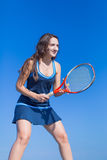 Girl with tennis racquet in hands posing against clear sky Royalty Free Stock Images