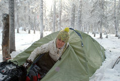 Girl tent camping in the snow. Young woman camping in a tent in the winter forest stock images