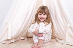 Girl at the tent. Portrait of a little smiling girl sitting on the floor near the tent and hugging her knees stock image