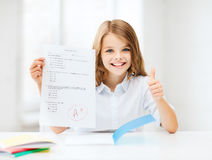 Girl with test and grade at school. Education and school concept - little student girl with test and A grade showing thumbs up at school Royalty Free Stock Image