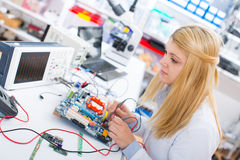 Girl with a tester and a printed circuit Royalty Free Stock Photos
