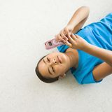 Girl text messaging. Asian preteen girl lying on back on floor text messaging on cell phone Royalty Free Stock Image