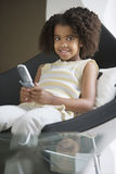Girl (5-7) text messaging on mobile phone, sitting in chair, smiling, portrait Stock Images