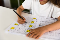 Girl with textbook. Young caucasian girl doing her homework while sitting at table Royalty Free Stock Photography