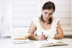 Girl with textbooks prepares for examinations at the university. Young brunette teaches lessons. Woman at the session. A student at the hostel reads books royalty free stock photography
