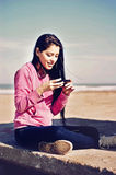 Girl texting  in the beach. Teenager sitting in the beach with her cellphone in hands in Mar del Plata, Argentina Royalty Free Stock Image
