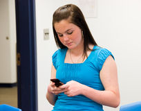 Girl texting in a classroom Stock Images