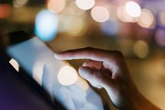 Girl texting finger on screen smartphone on background illumination glow bokeh light in night atmospheric city, hipster using in f. Emale hands mobile phone royalty free stock photo