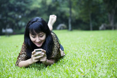 Girl texting in the park. Asian girl is texting while laying on the grass Royalty Free Stock Images