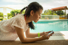 Girl texting at pool side. Pool day sunny Royalty Free Stock Images
