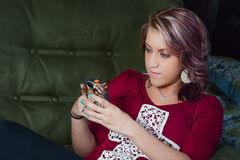 Girl Texting sitting in recliner Stock Images
