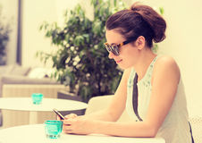 Girl texting on the smart phone in a hotel restaurant terrace Stock Photos