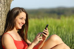 Girl texting in a smart phone relaxed in the country Stock Image