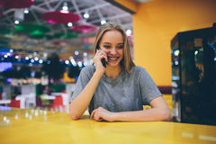 Girl texting on the smart phone in a restaurant terrace with an unfocused background Royalty Free Stock Photos