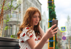 Girl texting on the smart phone sitting Royalty Free Stock Images