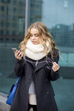 Girl texting on the smart phone in the street wearing Royalty Free Stock Image