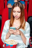 Girl texting sms in cinema Royalty Free Stock Images
