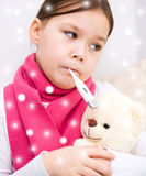 Girl with thermometer in her mouth Stock Photo