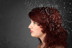 Girl thinking with abstract icons on her head Stock Photos