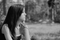Girl thinking in b&w. Thinking young woman alone in a park Royalty Free Stock Image