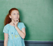 Girl thinking at chalkboard Stock Image