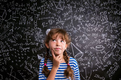 Girl  thinking, finger on cheek, blackboard with mathematical sy Stock Photos