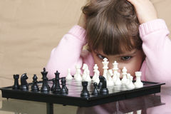 Girl thinking over chess Royalty Free Stock Images