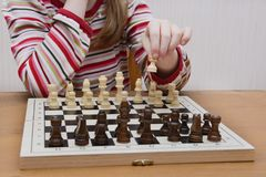 The girl thinks through a course in wooden chess stock photography