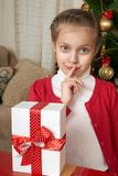 Girl thinks about a gift near christmas tree, happy holiday and winter celebration Stock Image