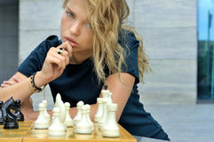 Girl thinks how to make a move on the chessboard. Outdoors She has long blonde hair and she is beautiful Stock Photography