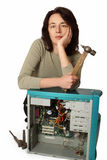 The girl thinks how to repair a computer. The girl holds a hammer in a hand, and sits at the disassembled old computer Royalty Free Stock Photos